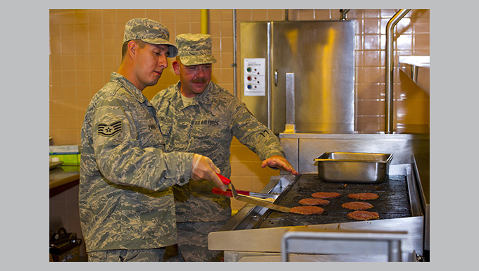 Staff Sgt. Reese and Staff Sgt. Parra grill hamburger patties