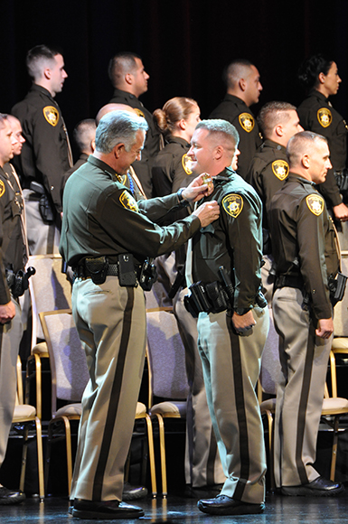 Senior Airman Brett Clashman receives his police officer badge