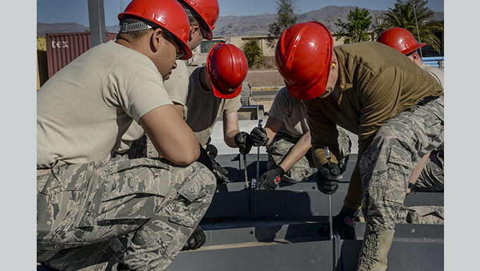 RED HORSE personnel tighten tighten bolts on the roof structure